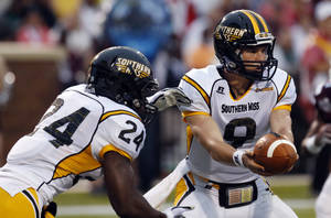 Photo - Southern Mississippi quarterback Nick Mullens (9) hands off to running back George Payne (24) in the first quarter of an NCAA college football game against Mississippi State at Davis Wade Stadium in Starkville, Miss., Saturday, Aug. 30, 2014. (AP Photo/Rogelio V. Solis)