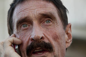 photo - Software company founder John McAfee talks on his mobile phone after a press conference outside the Supreme Court in Guatemala City, Tuesday, Dec. 4, 2012. McAfee, 67, who has been identified as a &quot;person of interest&quot; in the killing of his neighbor in Belize, 52-year-old Gregory Faull, has surfaced in public for the first time in weeks, saying Tuesday that he plans to ask for asylum in Guatemala because he fears persecution in Belize. (AP Photo/Moises Castillo)