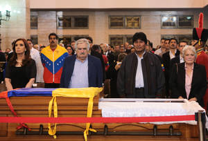 Photo - In this photo released by Miraflores Press Office, Argentina's President Cristina Fernandez, left, Venezuela's interim President Nicolas Maduro, second from left,  Uruguay's President Jose Mujica, third from left, Bolivia's President Evo Morales, fourth from left, and Mujica's wife, Uruguayan Senator Lucía Topolansky stand next to the flag-draped coffin containing the body of Venezuela's late President Hugo Chavez on display during his wake in Fort Tiuna military academy where his body will lie in state in Caracas, Venezuela, Wednesday, March 6, 2013. Seven days of mourning were declared, all schools were suspended for the week and friendly heads of state were expected for an elaborate funeral Friday. (AP Photo/Miraflores Presidential Press Office)