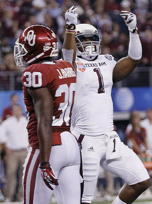 photo - Texas A&M's Ben Malena (1) celebrates a touchdown in front of Oklahoma's Javon Harris (30) during the college football Cotton Bowl game between the University of Oklahoma Sooners (OU) and Texas A&M University Aggies (TXAM) at Cowboy's Stadium on Friday Jan. 4, 2013, in Arlington, Tx. Photo by Chris Landsberger, The Oklahoman