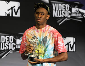 Photo - FILE - This Aug. 28, 2011 file photo shows Tyler the Creator posing backstage with the award for best new artist backstage at the MTV Video Music Awards in Los Angeles. PepsiCo said it immediately pulled the 60-second Mountain Dew ad after learning that people found it was offensive. The ad was part of a series developed by African-American rapper Tyler, The Creator, and depicted a battered white woman on crutches being urged to identify a suspect out of a lineup of black men.(AP Photo/Chris Pizzello, file)