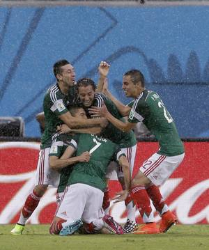 Photo - Mexico's Oribe Peralta celebrates with teammates after scoring the opening goal during the group A World Cup soccer match between Mexico and Cameroon in the Arena das Dunas in Natal, Brazil, Friday, June 13, 2014.  (AP Photo/Ricardo Mazalan)