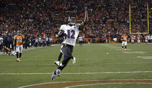 Photo - Baltimore Ravens wide receiver Jacoby Jones celebrates as he crosses the goal line for a touchdown against the Denver Broncos in the fourth quarter of an AFC divisional playoff NFL football game, Saturday, Jan. 12, 2013, in Denver. (AP Photo/Joe Mahoney)
