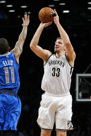 Photo - Brooklyn Nets power forward Mirza Teletovic (33) shoots a three point shot over Dallas Mavericks shooting guard Monta Ellis (11) in the second quarter of an NBA basketball game on Friday, Jan. 24, 2014, in New York. (AP Photo/Paul J. Bereswill)