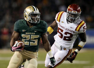 Photo - Baylor 's Lache Seastrunk (25) runs the ball as Iowa State 's Jeremiah George (52) gives chase in the first half of an NCAA college football game, Saturday, Oct. 19, 2013, in Waco, Texas. (AP Photo/Tony Gutierrez)