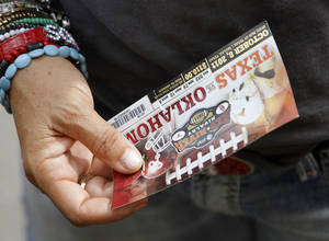 photo - An Oklahoma fan holds their ticket during the Red River Rivalry college football game between the University of Oklahoma Sooners (OU) and the University of Texas Longhorns (UT) at the Cotton Bowl in Dallas, Saturday, Oct. 8, 2011. Photo by Chris Landsberger, The Oklahoman  ORG XMIT: KOD