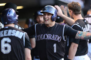 Photo - Colorado Rockies' Corey Dickerson, left, congratulates Brandon Barnes after his two-run home run against the Miami Marlins in the third inning of a baseball game in Denver on Saturday, Aug. 23, 2014. (AP Photo/David Zalubowski)