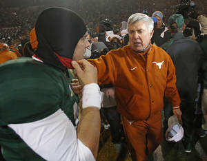 Photo - Texas head coach Mack Brown congratulates Baylor quarterback Bryce Petty after the Bears' 30-10 win during the University of Texas Longhorns vs. the Baylor University Bears NCAA football game at Floyd Casey Stadium in Waco, Texas on Saturday, Dec. 7, 2013.  (Fuyang DeLuca/Special Contributor)