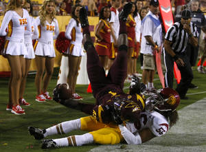 Photo - Arizona State running back Marion Grice (1) scores a touchdown over Southern California linebacker Anthony Sarao (56) during the first half of an NCAA college football game on Saturday, Sept. 28 2013, in Tempe, Ariz. (AP Photo/Rick Scuteri)