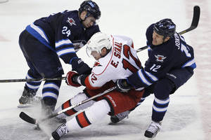 Photo - Winnipeg Jets' Grant Clitsome (24) and Olli Jokinen (12) double-team Carolina Hurricanes' Eric Staal (12) during the second period of their NHL hockey game in Winnipeg, Manitoba, Thursday, April 18, 2013. (AP Photo/The Canadian Press, John Woods)