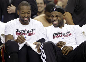 Photo - Miami Heat's Dwayne Wade,left, and LeBron James sit together on the bench in the closing moments of their NBA basketball game against the Sacramento Kings in Sacramento, Calif., Saturday, Jan. 12, 2013.  The Heat won 128-99. (AP Photo/Rich Pedroncelli)