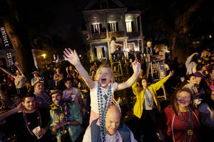 photo - Addison Moran, 7, yells for beads and trinket from the shoulders of her father Paul Moran during the Krewe of Bacchus Mardi Gras parade in New Orleans, Sunday, Feb. 10, 2013. (AP Photo/Gerald Herbert)