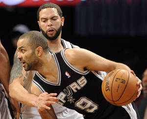 Photo - San Antonio Spurs' Tony Parker (9) drives the ball against Brooklyn Nets' Deron Williams (8) in the first half of an NBA basketball game, Sunday, Feb. 10, 2013, at Barclays Center in New York. The Spurs won 111-86. (AP Photo/Kathy Kmonicek)