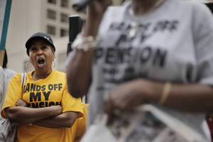 "Photo - Retiree Evelyn Smith, left, protests near the federal courthouse in Detroit, Thursday, July 3, 2014. Ballots submitted by city workers, retirees, pensioners and other creditors likely will determine how quickly Detroit exits its historic bankruptcy. The city's two pension groups have been pushing their members to vote ""yes"" on a restructuring plan that seeks to cut their income. Rejection of the plan could lead to what's known as a cram down and steeper reduction in pension payments. (AP Photo/Paul Sancya)"