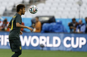 Photo - Brazil's Neymar plays with the ball during an official training session the day before the group A World Cup soccer match between Brazil and Croatia in the Itaquerao Stadium in Sao Paulo, Brazil, Wednesday, June 11, 2014. (AP Photo/Kirsty Wigglesworth)