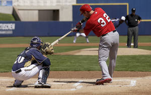 photo - Los Angeles Angels' Josh Hamilton grounds out as Milwaukee Brewers catcher Jonathan Lucroy watches during the first inning of a spring training baseball game in Phoenix, Tuesday, March 19, 2013. The second base umpire, Jim Joyce, called ball and strikes for part of the first inning after home plate umpire Seth Buckminster was hit with a pitch and left the game. (AP Photo/Chris Carlson)
