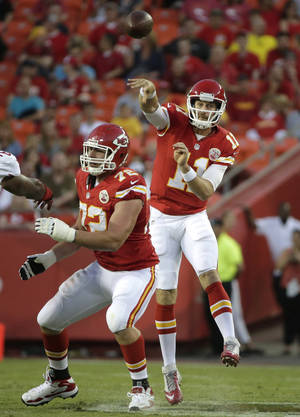 Photo - Kansas City Chiefs quarterback Alex Smith (11) passes behind the blocking of offensive tackle Eric Fisher (72) during the first half of an preseason NFL football game against the San Francisco 49ers at Arrowhead Stadium in Kansas City, Mo., Friday, Aug. 16, 2013. (AP Photo/Charlie Riedel)