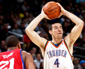 Photo - Oklahoma City's Nick Collison, right, looks for an open teammate against Philadelphia's defense during the second half Wednesday. Photo By John Clanton, The Oklahoman