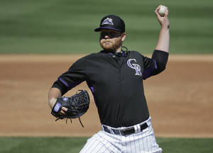 Photo - Colorado Rockies starting pitcher Brett Anderson throws against the Oakland Athletics during the second inning of a spring training baseball game in Scottsdale, Ariz., Saturday, March 8, 2014. (AP Photo/Chris Carlson)