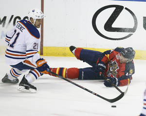 Photo - Edmonton Oilers' Andrew Ference (21) and Florida Panthers' Tomas Fleischmann (14) battle for the puck during the first period of an NHL hockey game in Sunrise, Fla., Tuesday, Nov. 5, 2013. (AP J Pat Carter)