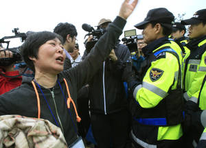 Photo - A weeping relative of a missing passenger aboard the sunken ferry Sewol shouts as she tries to march toward the presidential house to protest the government's rescue operation in Jindo, South Korea, Sunday, April 20, 2014. After more than three days of frustration and failure, divers on Sunday finally found a way into the submerged ferry off South Korea's southern shore, discovering more than a dozen bodies inside the ship and pushing the confirmed death toll to over four dozen, officials said. (AP Photo/Ahn Young-joon)