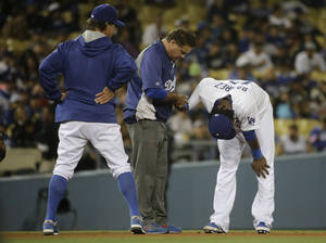 Photo - Los Angeles Dodgers manager Don Mattingly, left, watches as Hanley Ramirez, right, is tended to by trainer Stan Conte after Ramirez hurt his hand during the seventh inning of a baseball game against the Colorado Rockies on Tuesday, June 17, 2014, in Los Angeles. (AP Photo/Jae C. Hong)