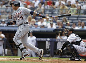 Photo - Detroit Tigers' Miguel Cabrera (24) follows through on a single during the first inning of a baseball game New York Yankees catcher Austin Romine looks on Saturday, Aug. 10, 2013, in New York. (AP Photo/Frank Franklin II)