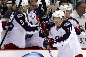 Photo - Columbus Blue Jackets' Matt Calvert (11) returns to the bench after his short-handed goal in the second period of a first-round NHL playoff hockey game against the Pittsburgh Penguins in Pittsburgh on Saturday, April 19, 2014. (AP Photo/Gene J. Puskar)