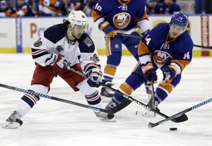 Photo - New York Rangers' Mats Zuccarello (36) and New York Islanders' Thomas Hickey (14) fight for control of the puck during the second period of an NHL hockey game on Friday, Jan. 31, 2014, in New York. (AP Photo/Frank Franklin II)