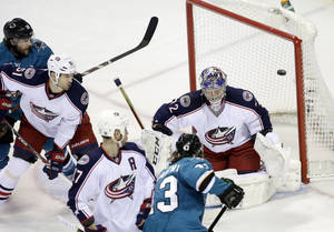 Photo - San Jose Sharks' John McCarthy, bottom right, scores past Columbus Blue Jackets goalie Sergei Bobrovsky, top right, during the first period of an NHL hockey game, Friday, Feb. 7, 2014, in San Jose, Calif. (AP Photo/Marcio Jose Sanchez)