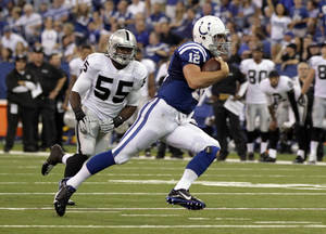 Photo - Indianapolis Colts quarterback Andrew Luck runs past Oakland Raiders outside linebacker Sio Moore on his way to a touchdown during the second half of an NFL football game in Indianapolis, Sunday, Sept. 8, 2013. (AP Photo/AJ Mast)