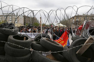 Photo - People stand at a barricade at the regional administration building that they had seized earlier in Donetsk, Ukraine, Sunday, April 20, 2014. The Ukrainian and Russian governments are reporting a shootout at a checkpoint set up by pro-Russian insurgents in eastern Ukraine that has left one person dead and others hospitalized with gunshot wounds. (AP Photo/Sergei Grits)