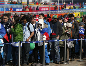 Photo - People wait in a long line outside a gift shop at Olympic Park during the 2014 Winter Olympics, Monday, Feb. 17, 2014, in Sochi, Russia. (AP Photo/Julio Cortez)