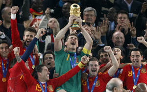 "Photo - FILE _ This is a file photo of  Spain's goalkeeper Iker Casillas, center, as he holds up the World Cup trophy with team members as they celebrate their victory at the end of the World Cup final soccer match between the Netherlands and Spain at Soccer City in Johannesburg, South Africa. Winning the soccer World Cup can bring instant rewards to that country's stock market investors. But they better be quick as the post-victory rally doesn't last long.  That's the conclusion of investment bank Goldman Sachs, which published a wide-ranging report late Tuesday  May 27, 2014 on the World Cup and its economic impact. Goldman Sachs analysts found ""a clear pattern of out performance by the wining team in the weeks after the World Cup final."" On average, the investment bank's portfolio strategy team the victor outperforms the global market by 3.5 percent in the first month.  (AP Photo/Luca Bruno, File)"