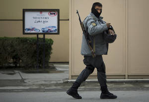 Photo - An Afghan policeman patrols the entrance of the Serena hotel in downtown Kabul, Afghanistan, Friday, March 21, 2014. Four men with pistols stuffed in their socks attacked the hotel in Kabul on Thursday, opening fire in a restaurant and killing nine people, including four foreigners, officials said. (AP Photo/Anja Niedringhaus)