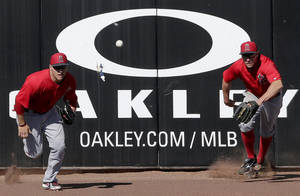 photo - Los Angeles Angels left fielder Mike Trout, left, and center fielder Peter Bourjos chase after a triple hit by Seattle Mariners' Dustin Ackley during an exhibition spring training baseball game, Monday, Feb. 25, 2013, in Peoria, Ariz. (AP Photo/Charlie Riedel)