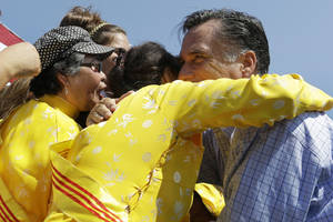 "Photo -   Republican presidential candidate, former Massachusetts Gov. Mitt Romney embraces women wearing traditional Vietnamese ""ao dai"" dresses as he campaigns at Van Dyck Park in Fairfax, Va., Thursday, Sept. 13, 2012. (AP Photo/Charles Dharapak)"