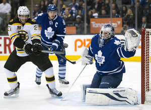 Photo - Toronto Maple Leafs goaltender James Reimer, right, prepares to make a glove save as Boston Bruins right winger Loui Eriksson (21) tries to deflect the shot while Leafs defenseman Dion Phaneuf (3) skates near during an overtime period of an NHL hockey game in Toronto on Thursday, April 3, 2014. (AP Photo/The Canadian Press, Frank Gunn)