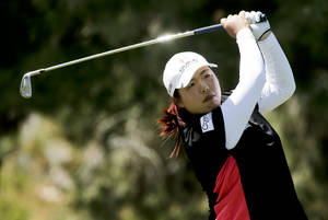 Photo - Shanshan Feng, of China, watches her tee shot on the 17th hole during the first round at the Kraft Nabisco Championship golf tournament on Thursday, April 3, 2014, in Rancho Mirage, Calif. (AP Photo/Chris Carlson)