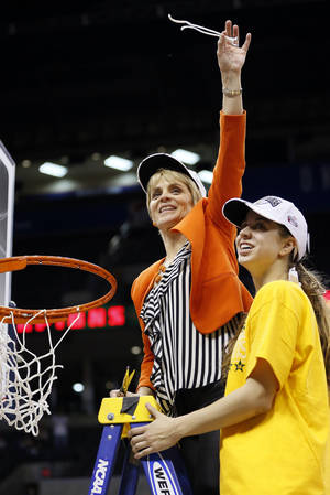 Photo - Baylor head coach Kim Mulkey holds up a piece of the net next to daughter Makenzie Robertson (14) after the Big 12 women's basketball tournament championship game between Baylor and West Virginia at the Chesapeake Energy Arena in Oklahoma City, Monday, March 10, 2014. Baylor won, 74-71. Photo by Nate Billings, The Oklahoman