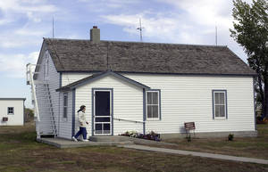 Photo - FILE - In this Oct. 10, 2002 file photo Edna Schwab walks toward the front door of Lawrence Welk's boyhood home in Strasburg, N.D. Volunteers are being recruited to help make repairs to the home. The three-day effort begins on Aug. 1, 2014. The state Historical Society voted in January to buy the homestead from Welk's nieces. The purchase agreement was contingent on negotiated repairs being made to the property, which is listed on the National Register of Historic Places. (AP Photo/Will Kincaid, File)