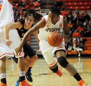 Photo - Oklahoma State guard Brittany Atkins dribbles to the lane during the Cowgirl's conference opener against West Virginia. West Virginia went on to defeat Oklahoma State 71-67 at Gallagher Iba Arena in Stillwater on Jan. 4, 2014.   Photo by KT King/For the Oklahoman