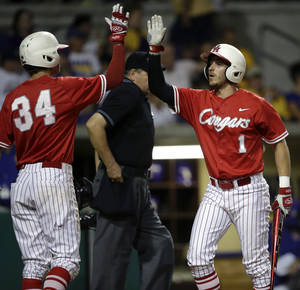 Photo - Houston's Landon Appling (1) is greeted by Kyle Survance (34) after Appling scored on an RBI single by Ashford Fulmer in the third inning of an NCAA college baseball regional tournament game against LSU in Baton Rouge, La., Monday, June 2, 2014. (AP Photo/Gerald Herbert)