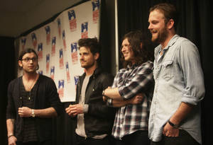 Photo - Above: The Kings of Leon band members, from left, Nathan, Jared, Matthew and Caleb  Followill, accept the  Oklahoma Music Hall of Fame's Rising Star award Friday at the BOK Center in Tulsa.