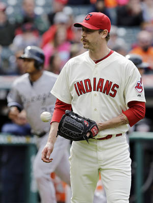 Photo - Cleveland Indians relief pitcher John Axford gets a new ball after giving up a three-run home run to Chicago White Sox's Dayan Viciedo in the ninth inning of a baseball game Sunday, May 4, 2014, in Cleveland. Axford took the loss as Chicago won 4-3. (AP Photo/Mark Duncan)