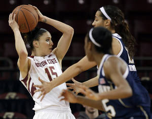 Photo - Boston College guard Lauren Engeln (15) looks for a way around the defense of Notre Dame guard Lindsay Allen, foreground, and forward Taya Reimer during the second half of an NCAA college basketball game in Boston, Thursday, Feb. 13, 2014. Notre Dame won 82-61. (AP Photo/Stephan Savoia)