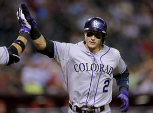 Photo - Colorado Rockies' Troy Tulowitzki, left, rounds the bases after hitting a solo home run against the Arizona Diamondbacks during the sixth inning of a baseball game on Monday, April 28, 2014, in Phoenix. (AP Photo/Matt York)