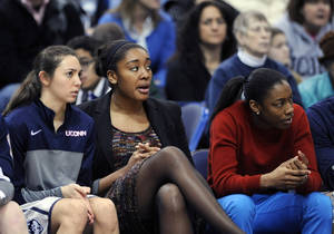 Photo - Briana Pulido, Morgan Tuck and Brianna Banks, left to right, watch action during the second half of Connecticut's 81-53 victory over South Florida in an NCAA college basketball game in Hartford, Conn., Sunday, Jan. 26, 2014. (AP Photo/Fred Beckham)