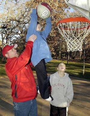 Photo - In this December 2003 photo, Dane Cole helps his daughter, Chandler, make a slam dunk while son Colton watches. File photo