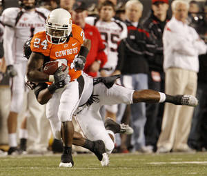 Photo - Kendall Hunter (24) drags Julius Howard (13) for a gain during the college football game between Oklahoma State University (OSU) and Texas Tech University (TT) at Boone Pickens Stadium in Stillwater, Okla. Saturday, Nov. 14, 2009.  Photo by Doug Hoke, The Oklahoman